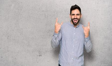 Elegant man with shirt making rock gesture over textured wall Banco de Imagens