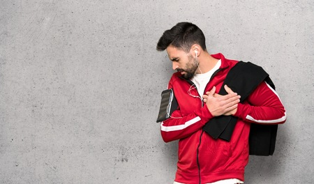 Handsome sportman having a pain in the heart over textured wall Imagens