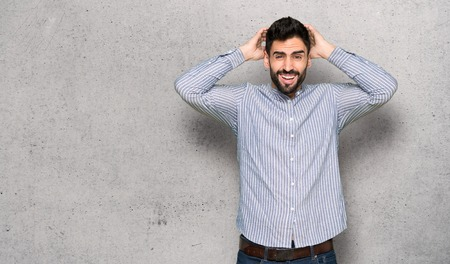 Elegant man with shirt takes hands on head because has migraine over textured wall