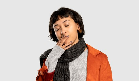 Short hair woman with coat yawning and covering wide open mouth with hand on isolated grey background
