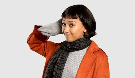 Short hair woman with coat having doubts while scratching head on isolated grey background
