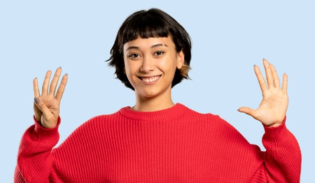 Short hair girl with red sweater counting nine with fingers on isolated blue background
