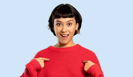 Short hair girl with red sweater with surprise facial expression on isolated blue background