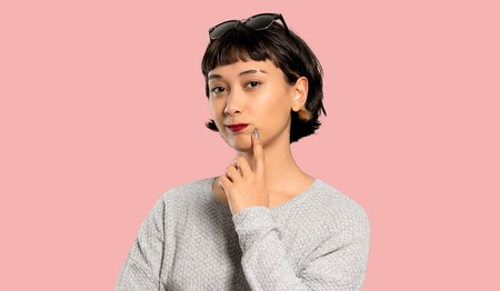 Young woman with short hair thinking on isolated pink background