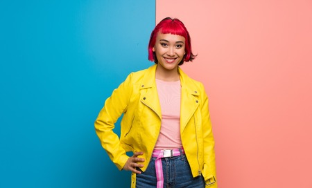 Young woman with yellow jacket posing with arms at hip and smiling