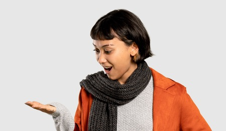 Short hair woman with coat holding copyspace imaginary on the palm to insert an ad on isolated grey background