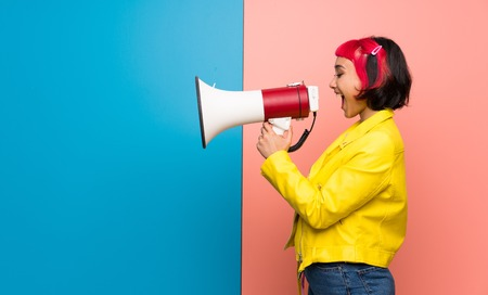 Young woman with yellow jacket shouting through a megaphone