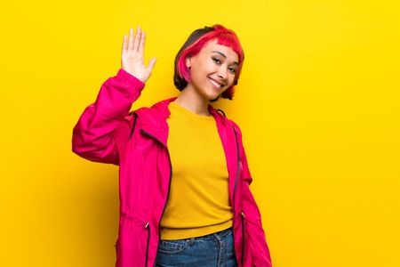 Young woman with pink hair over yellow wall saluting with hand with happy expression Banco de Imagens - 120973384