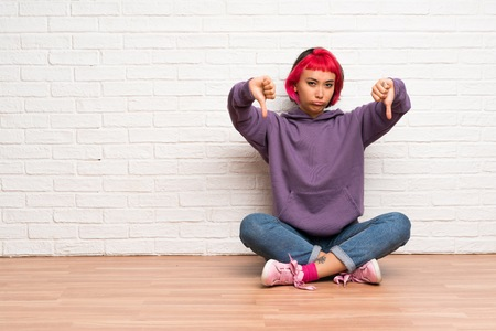 Young woman with pink hair sitting on the floor showing thumb down