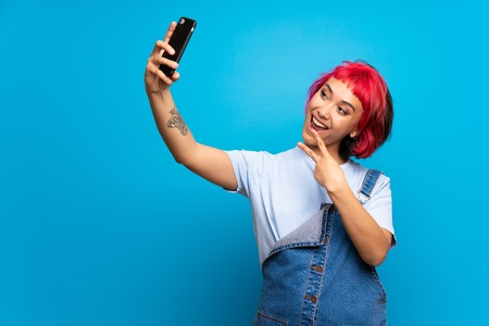 Young woman with pink hair over blue wall making a selfie