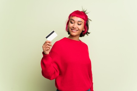 Young woman with red sweater holding a credit card and thinking