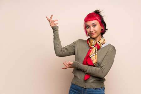 Young woman with pink hair over yellow wall extending hands to the side for inviting to come Standard-Bild