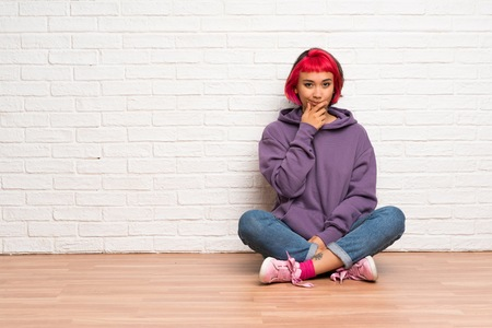 Young woman with pink hair sitting on the floor thinking 免版税图像
