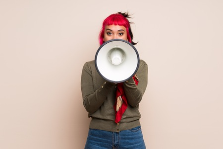 Young woman with pink hair over yellow wall shouting through a megaphone Imagens