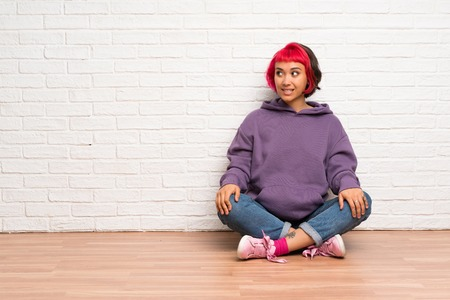 Young woman with pink hair sitting on the floor with confuse face expression