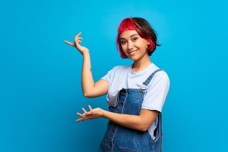 Young woman with pink hair over blue wall extending hands to the side for inviting to come