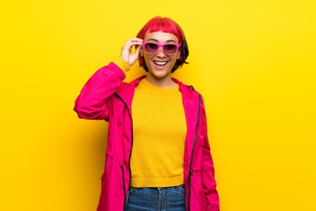 Young woman with pink hair over yellow wall with glasses and surprised