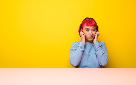 Young woman with pink hair frustrated and covering ears Reklamní fotografie