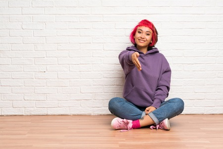 Young woman with pink hair sitting on the floor shaking hands for closing a good deal