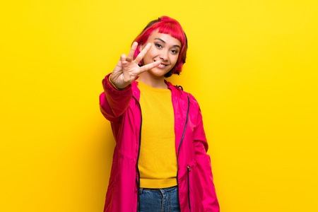 Young woman with pink hair over yellow wall happy and counting three with fingers Banco de Imagens