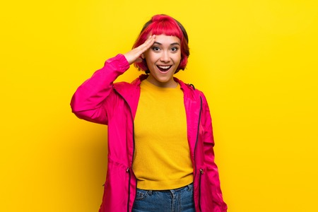 Young woman with pink hair over yellow wall has just realized something and has intending the solution