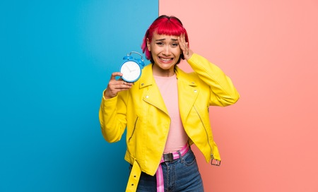 Young woman with yellow jacket restless because it has become late and holding vintage alarm clock