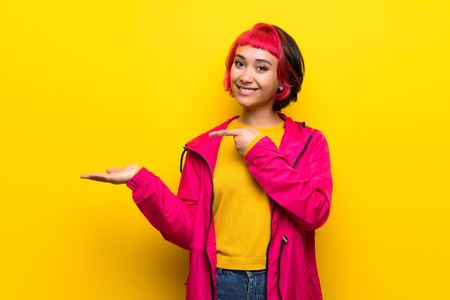 Young woman with pink hair over yellow wall holding copyspace imaginary on the palm to insert an ad