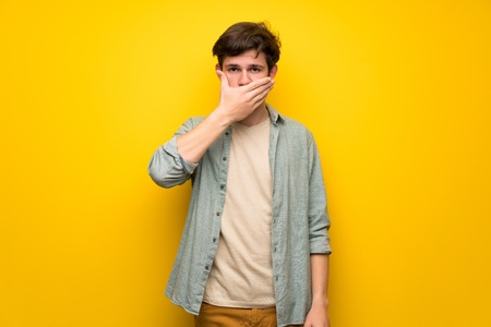 Teenager man over yellow wall covering mouth with hands for saying something inappropriate