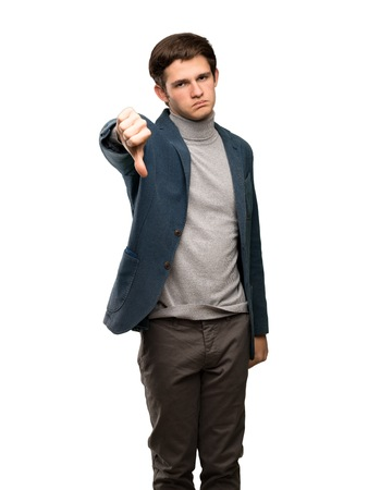 Teenager man with turtleneck showing thumb down with negative expression over isolated white background 版權商用圖片