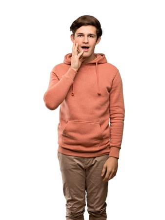 Teenager man with sweatshirt with surprise and shocked facial expression over isolated white background