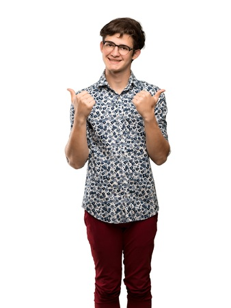 Teenager man with flower shirt and glasses giving a thumbs up gesture and smiling over isolated white background
