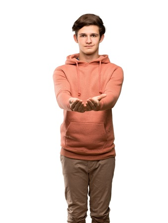 Teenager man with sweatshirt holding copyspace imaginary on the palm to insert an ad over isolated white background