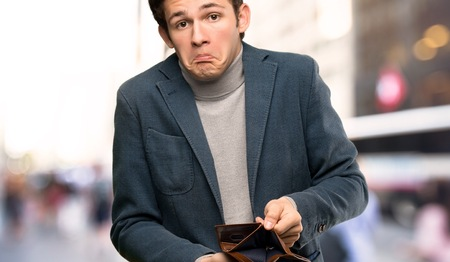 Teenager man with turtleneck holding a wallet at outdoors