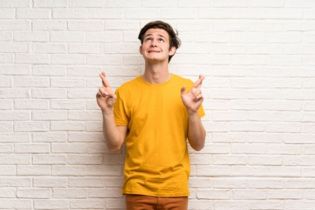 Teenager man over white brick wall with fingers crossing and wishing the best
