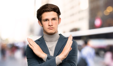 Teenager man with turtleneck making NO gesture at outdoors Stock Photo