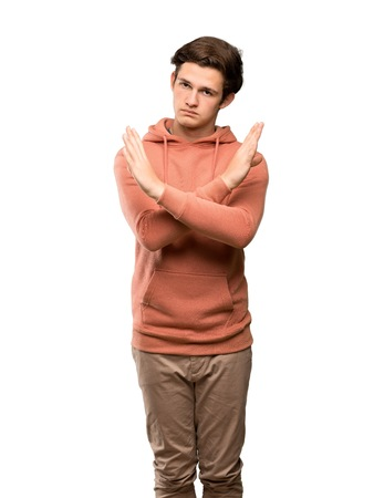 Teenager man with sweatshirt making NO gesture over isolated white background 版權商用圖片