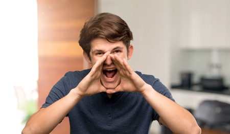Teenager man shouting and announcing something at indoors Imagens