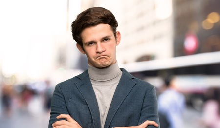 Teenager man with turtleneck feeling upset at outdoors