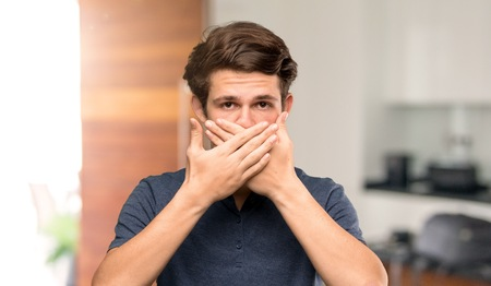 Teenager man covering mouth with hands for saying something inappropriate at indoors Banco de Imagens