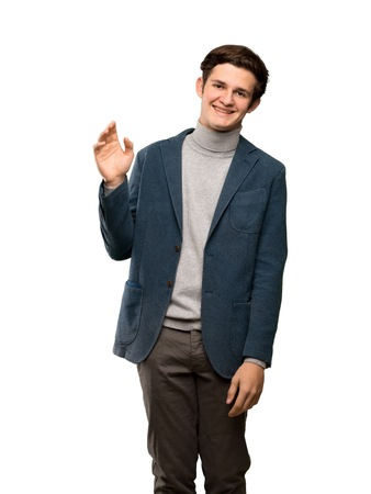 Teenager man with turtleneck saluting with hand with happy expression over isolated white background