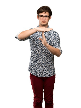 Teenager man with flower shirt and glasses making time out gesture over isolated white background