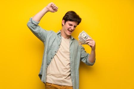 Hombre adolescente sobre pared amarilla tomando un montón de dinero