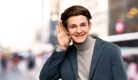 Teenager man with turtleneck listening to something by putting hand on the ear at outdoors