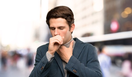 Teenager man with turtleneck is suffering with cough and feeling bad at outdoors