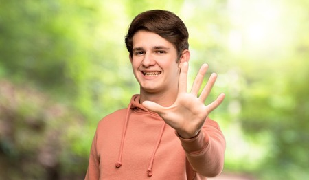 Teenager man with sweatshirt counting five with fingers at outdoors Stock Photo