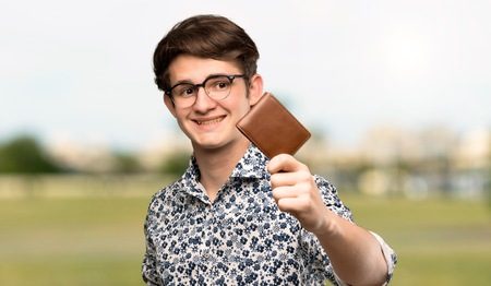 Teenager man with flower shirt and glasses holding a wallet at outdoors Stock Photo