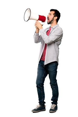 Full-length shot of Handsome man with beard shouting through a megaphone over isolated white background Imagens