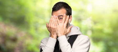 Sport man covering eyes by hands and looking through the fingers in a park