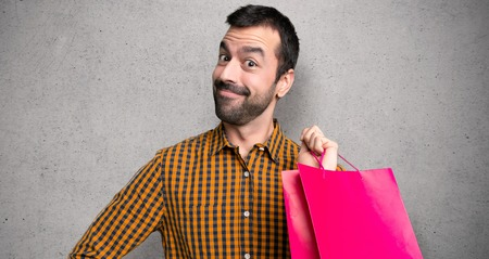 Man with shopping bags posing with arms at hip and laughing looking to the front over textured wall