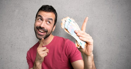 Man taking a lot of money pointing with the index finger and looking up over textured wall
